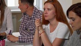 Κοκκινομάλλης γυναίκα που φαίνεται ενοχλημένη εργαζόμενη σε ένα πρόγραμμα στο σχολείο απόθεμα βίντεο