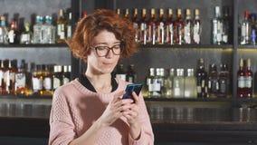 Κοκκινομάλλης γυναίκα που χρησιμοποιεί το smartphone στο εστιατόριο που στέκεται κοντά στη στάση φραγμών φιλμ μικρού μήκους