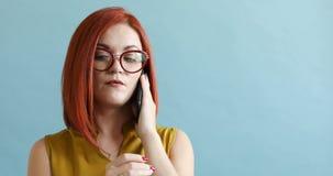 Κοκκινομάλλης γυναίκα στα γυαλιά που μιλούν στο τηλέφωνο κλήσης στο μπλε υπόβαθρο φιλμ μικρού μήκους