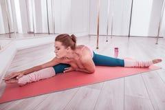 Κοκκινομάλλης λεπτή και κατάλληλη γυναίκα που φορά τις comfy περικνημίδες που τεντώνουν το σώμα της στοκ φωτογραφία με δικαίωμα ελεύθερης χρήσης