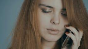 Κοκκινομάλλης νέα γυναίκα που μιλά στο τηλέφωνο και που χαμογελά στο υπόβαθρο στούντιο, συγκινήσεις έννοιας, επικοινωνία, τεχνολο απόθεμα βίντεο
