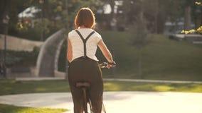 Κοκκινομάλλης ποδηλάτης γυναικών που οδηγά ένα ποδήλατο κατά την πίσω άποψη πάρκων πόλεων φιλμ μικρού μήκους