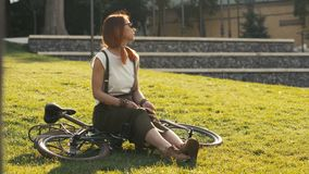 Κοκκινομάλλης συνεδρίαση γυναικών στο ποδήλατο που βρίσκεται στη χλόη στο πάρκο πόλεων Πάρκο ποδηλάτων γυναικών απόθεμα βίντεο