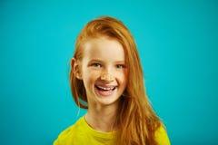 Κοκκινομάλλη κορίτσια γέλιου επτά έτη στο μπλε υπόβαθρο στοκ φωτογραφία