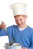 Κοκκινομάλλες αγόρι στο καπέλο του αρχιμάγειρα με την κουτάλα και το τηγάνι Στοκ εικόνα με δικαίωμα ελεύθερης χρήσης