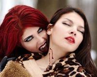 Κοκκινομάλλες βαμπίρ που δαγκώνει το αθώο κορίτσι στοκ εικόνες