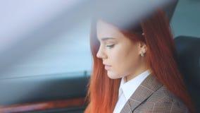 Κοκκινομάλλες καταπληκτικό πρότυπο κοκκινομάλλες κορίτσι στο καφετί σακάκι και λευκιά μπλούζα με τα βαθιά μπλε μάτια aqua που κάθ απόθεμα βίντεο