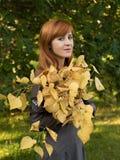 Κοκκινομάλλες κορίτσι με τα κίτρινα φύλλα Στοκ φωτογραφία με δικαίωμα ελεύθερης χρήσης