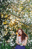 Κοκκινομάλλες κορίτσι με τις φακίδες κοντά στο δέντρο μηλιάς Στοκ φωτογραφία με δικαίωμα ελεύθερης χρήσης