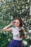 Κοκκινομάλλες κορίτσι με τις φακίδες κοντά στο δέντρο μηλιάς Στοκ φωτογραφίες με δικαίωμα ελεύθερης χρήσης