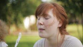 κοκκινομάλλες mom και σγουρός-μαλλιαρές φυσαλίδες χτυπήματος κορών στο πάρκο απόθεμα βίντεο