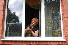 Κοκκινομάλλης γυναίκα με τη γάτα πίσω από το ανοικτό παράθυρο Στοκ Φωτογραφίες