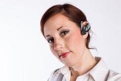 Κοκκινομάλλης γυναίκα με το ακουστικό Bluetooth Στοκ Εικόνες