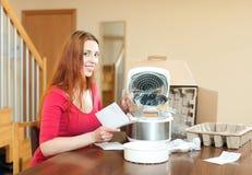 Κοκκινομάλλης γυναίκα με το ηλεκτρικό δοχείο αγγείων στην κουζίνα της στο σπίτι Στοκ Φωτογραφίες