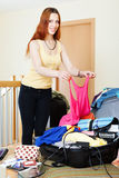 Κοκκινομάλλης γυναίκα που προσθέτει τα ενδύματα στις βαλίτσες Στοκ Φωτογραφία