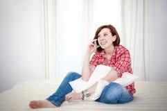 Κοκκινομάλλης γυναίκα στον καναπέ που μιλά στο κινητό κύτταρο Στοκ Εικόνα