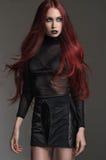 Κοκκινομάλλης γυναίκα στο απότομα μαύρο προκλητικό φόρεμα στοκ εικόνες