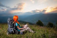 Κοκκινομάλλης κυρία με το σακίδιο πλάτης στα βουνά στο ηλιοβασίλεμα Στοκ Φωτογραφίες
