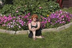 Κοκκινομάλλης μέσης ηλικίας γυναίκα στον κήπο λουλουδιών Στοκ φωτογραφία με δικαίωμα ελεύθερης χρήσης
