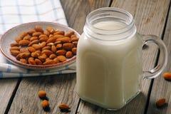 Κοκτέιλ γάλακτος αμυγδάλων στο βάζο με τα καρύδια αμυγδάλων στον αγροτικό ξύλινο πίνακα Εναλλακτικά τρόφιμα Vegan, μη γαλακτοκομι στοκ εικόνες με δικαίωμα ελεύθερης χρήσης