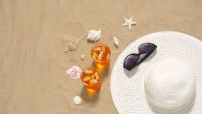 Κοκτέιλ, καπέλο ήλιων και γυαλιά ηλίου στην άμμο παραλιών απόθεμα βίντεο