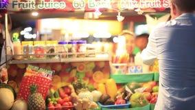 Κοκτέιλ νωπών καρπών στις ασιατικές αγορές οδών Ο νεαρός άνδρας αγοράζει έναν χυμό φρούτων 1920x1080 απόθεμα βίντεο