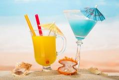 Κοκτέιλ, ποτήρι του χυμού από πορτοκάλι με τις ομπρέλες, κασετίνα με το αχλάδι Στοκ Εικόνες