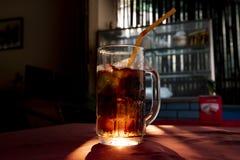 Κοκ inglass με το άχυρο Καφετί λαμπιρίζοντας ποτό με τον ήλιο backlight Λαμπιρίζοντας ποτό με τον πάγο στο γυαλί Στοκ εικόνες με δικαίωμα ελεύθερης χρήσης