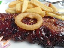 Κολλώδη πλευρά σχαρών με τα τσιπ, coleslaw και κρεμμυδιών τα δαχτυλίδια στοκ φωτογραφία