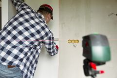 Κολλώντας τις ταπετσαρίες στο σπίτι Ο νεαρός άνδρας, εργαζόμενος βάζει επάνω τις ταπετσαρίες στον τοίχο Έννοια εγχώριας ανακαίνισ στοκ φωτογραφίες με δικαίωμα ελεύθερης χρήσης
