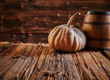 Κολοκύθα και βαρέλι στον παλαιό ξύλινο πίνακα στοκ εικόνες