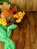 Κολοκύθα σε ένα ψάθινο καλάθι με τα λουλούδια, τη σορβιά και τα ξηρά φύλλα Στοκ φωτογραφία με δικαίωμα ελεύθερης χρήσης