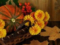 Κολοκύθα σε ένα ψάθινο καλάθι με τα λουλούδια, τη σορβιά και τα ξηρά φύλλα Στοκ Φωτογραφία