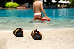 Κολυμπήστε τα παπούτσια δίπλα στη λίμνη με το παιχνίδι μικρών παιδιών με τη σφαίρα στο υπόβαθρο θαμπάδων στοκ εικόνες με δικαίωμα ελεύθερης χρήσης
