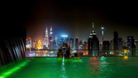 Κολύμβηση γυναίκας στην άκρη της πισίνας στεγών για να απολαύσει τη εικονική παράσταση πόλης νύχτας της Κουάλα Λουμπούρ, Μαλαισία φιλμ μικρού μήκους