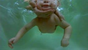 Κολύμβηση μωρών Εκμάθηση να κολυμπιέται ένα παιδί κάτω από 1 έτος Βουτώντας ένα νήπιο στο λουτρό κάτω από τη επίβλεψη ενός γιατρο απόθεμα βίντεο