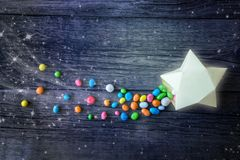 Κομήτης, μειωμένα χάπια καραμελών αστεριών γλυκά πολύχρωμα στο δώρο εγγράφου στοκ εικόνα με δικαίωμα ελεύθερης χρήσης