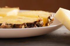 Κομμάτια ανανά με τη φλούδα σε ένα άσπρο πιάτο Στοκ Φωτογραφίες