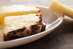 Κομμάτια ανανά με τη φλούδα σε ένα άσπρο πιάτο Στοκ Εικόνες
