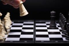 Κομμάτια ενός σκακιού που μένουν ενάντια στα μαύρα κομμάτια σκακιού Στοκ Εικόνες