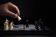 Κομμάτια ενός σκακιού που μένουν ενάντια στα μαύρα κομμάτια σκακιού Στοκ Φωτογραφίες