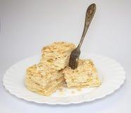 Κομμάτια κέικ σε ένα άσπρο υπόβαθρο σε ένα πιάτο με ένα δίκρανο Στοκ εικόνα με δικαίωμα ελεύθερης χρήσης