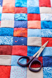 Κομμάτια μπλε και κόκκινων τετραγώνων του υφάσματος που συρράπτεται Στοκ Εικόνα