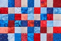 Κομμάτια μπλε και κόκκινων τετραγώνων του υφάσματος που συρράπτεται Στοκ Εικόνες
