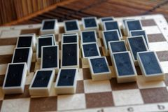 Κομμάτια ντόμινο μετά από την επίδραση ντόμινο, πίσω πλευρά, στο καφετί ξύλινο επιτραπέζιο υπόβαθρο μπαμπού Στοκ Φωτογραφίες