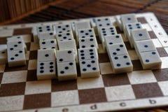 Κομμάτια ντόμινο μετά από την επίδραση ντόμινο στο καφετί ξύλινο επιτραπέζιο υπόβαθρο μπαμπού Στοκ εικόνα με δικαίωμα ελεύθερης χρήσης