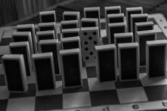 Κομμάτια ντόμινο σε μια σειρά και ένα διαφορετικό statnd, πίσω πλευρά, στο τ Στοκ φωτογραφία με δικαίωμα ελεύθερης χρήσης