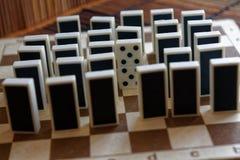 Κομμάτια ντόμινο σε μια σειρά και μια διαφορετική στάση, πίσω πλευρά, στο καφετί ξύλινο επιτραπέζιο υπόβαθρο μπαμπού Στοκ Φωτογραφία