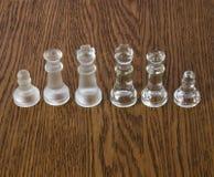 Κομμάτια σκακιού γυαλιού που στέκονται σε έναν ξύλινο πίνακα Στοκ Εικόνα