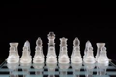 Κομμάτια σκακιού γυαλιού στην αρχική διαταγή πριν από το παιχνίδι σε ένα μαύρο υπόβαθρο χρυσή ιδιοκτησία βασικών πλήκτρων επιχειρ στοκ φωτογραφία με δικαίωμα ελεύθερης χρήσης